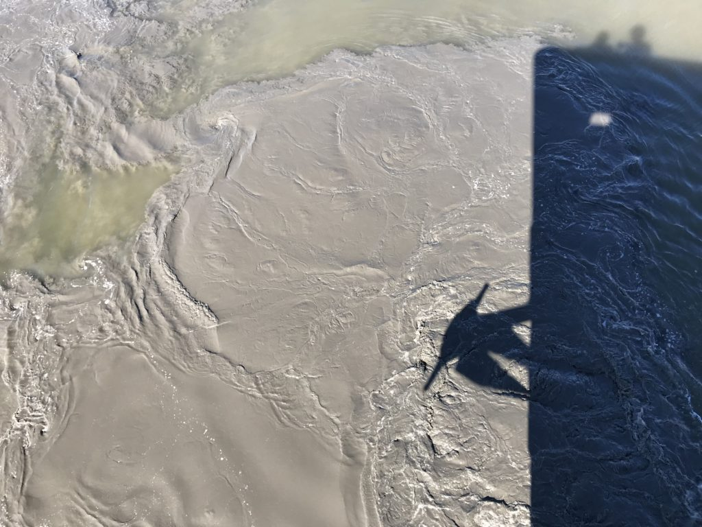 ship's shadow over silty water