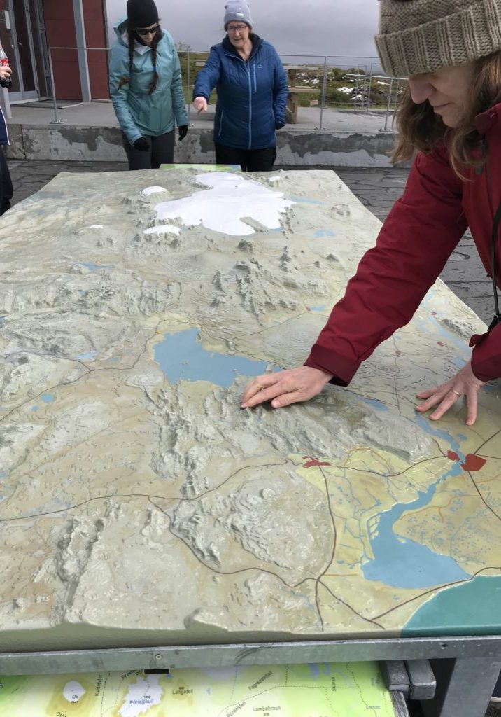 amy touches topographic table map of reykjanes ridge during iceland geological field trip