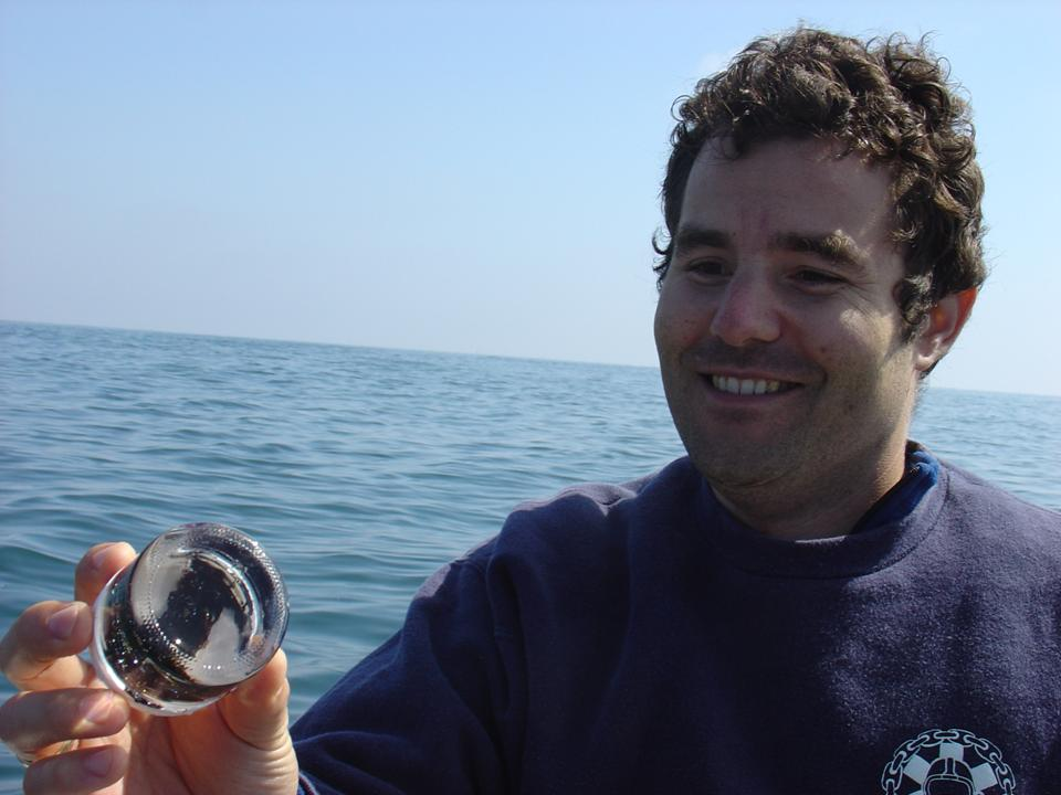 Dave Valentine (UCSB) aboard the R/V Connell and holding a recently-collected oil droplet